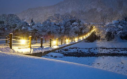 Обои Засыпанный снегом подвесной мост с горящими фонарями, проложенный через реку и ведущий в небольшой поселок у подножья горы