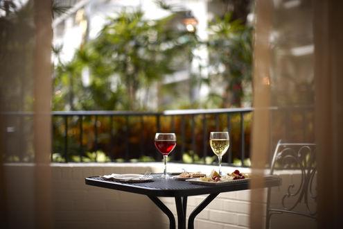 Обои Два бокала вина, сыр, виноград и печенье стоят на столика на балконе с видом на пальмы и другое здание