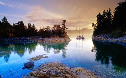 Обои Горное озеро с островами, стоящими на якоре лодками, с берегами. покрытыми деревьями, на фоне заката