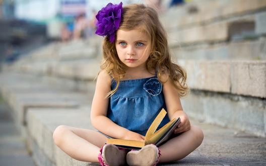 Обои Девочка с книгой сидит на ступеньках