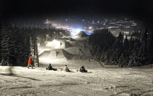 Обои Снежная горка  с освещением, созданная для катания на сноубордах и расположенная среди хвойных деревьев на  городской окраине