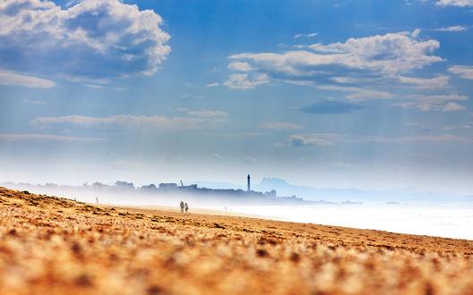 Обои Желтый пустынный пляж, над которым проплывают облака в чистом голубом небе