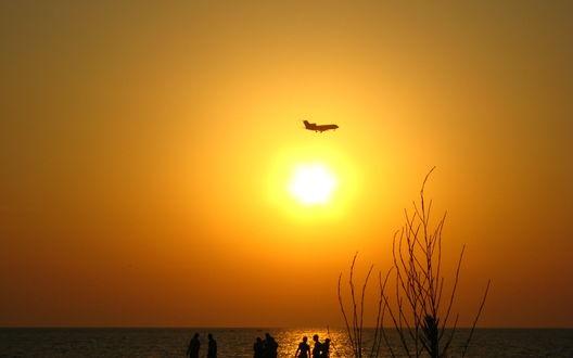 Обои Закат над морем, на берегц которого отдыхают люди, в небе пролетает самолет
