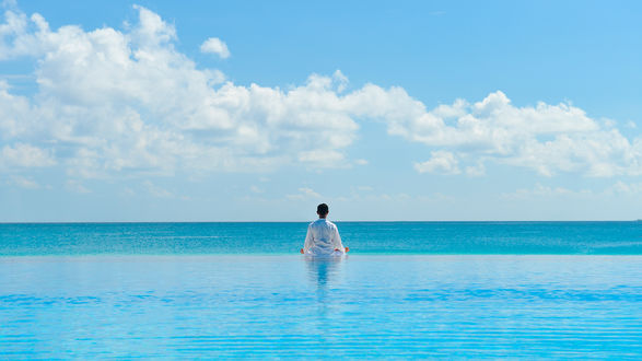 Обои Мужчина сидит на краю бассейна и смотрит на голубую воду и небо с облаками