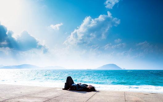 Обои Девушка лежит на берегу моря под голубым небом