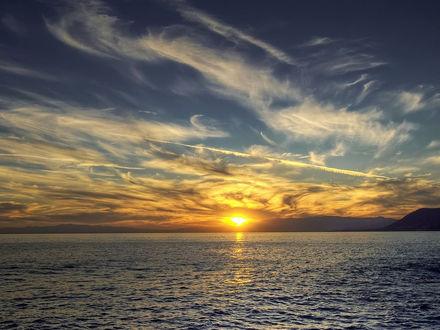 Обои Солнце заходит за скалистый берег моря