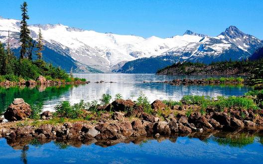 Обои Озеро с каменистыми берегами и деревьями на фоне голубого неба, горного массива, покрытого снегом