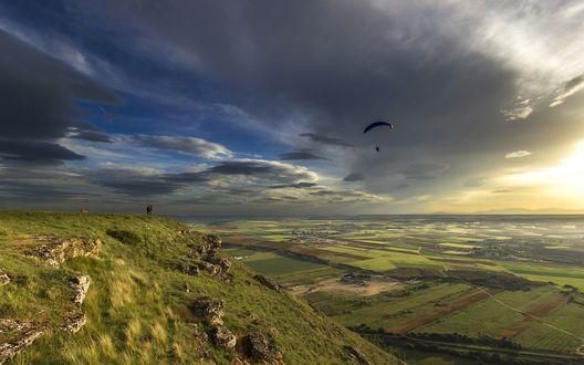 Обои Парашютист, спрыгнув со скалы, парит над полями и лугами в закатном небе