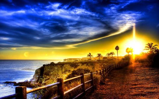 Обои Яркий луч света осветил дорогу со стоящим вдоль нее забором, идущую к городу, расположенному  на берегу моря
