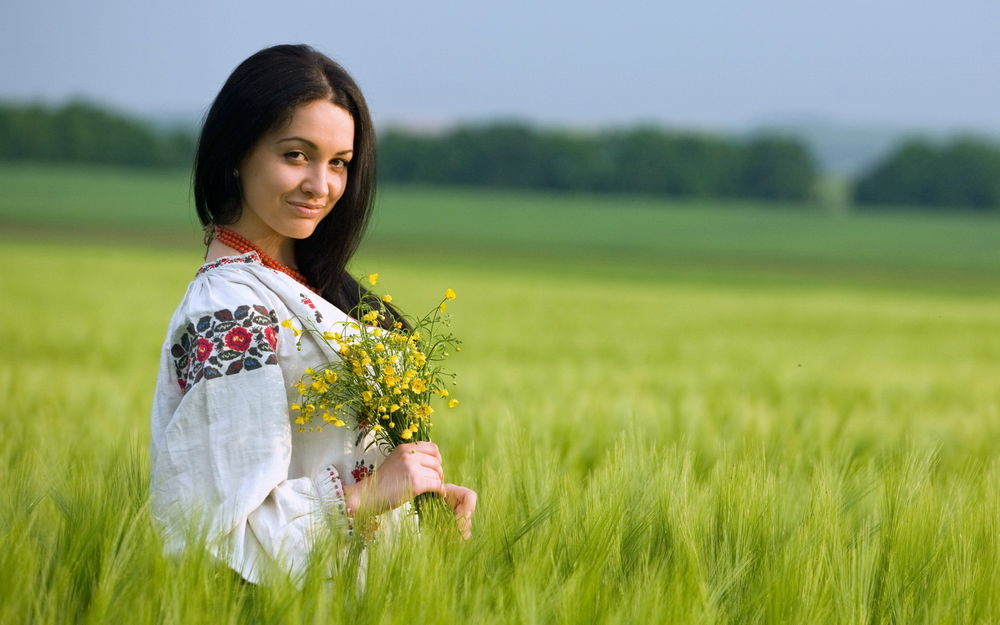 Обои для рабочего стола Девушка в белой рубахе стоит в поле в букетом цветов в руках