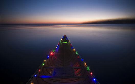 Обои На бортах лодки, плывущей по озеру, расположены горящие лампочки новогодней гирлянды