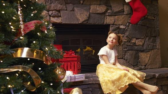Обои Девочка, сидящая у камина возле наряженной новогодней елки, ждет рождественских подарков