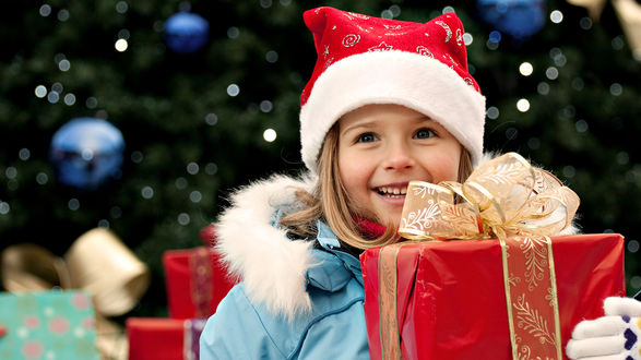 Обои Радостная девочка в шапке Санта-Клауса / Santa Klaus c  подарочной новогодней коробкой