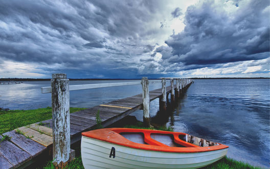 Обои Небольшая прогулочная лодка лежит на берегу озера возле деревянного причала