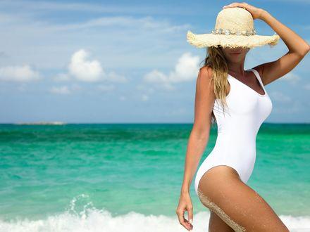 Обои Девушка в белом купальнике и соломенной шляпе стоит на берегу лазурного моря