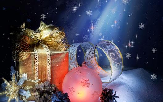 Обои Елочный шарик, блестящая лента, звездочки, шишки, праздничные подарки в красивых коробках, лежащие на снегу, на синем фоне со снежинками