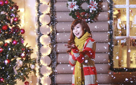 Обои Девушка азиатка стоит возле деревянного дома, украшенного к Новому году