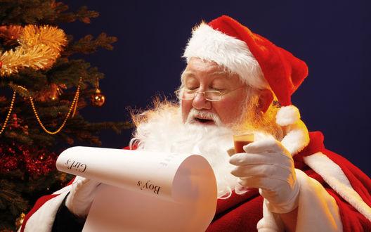 Обои Санта Клаус / Santa Claus читает список детей с поднятой в руке рюмкой
