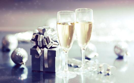 Обои Два бокала с шампанским стоят на столе возле новогоднего подарка, по столу разбросаны новогодние шары