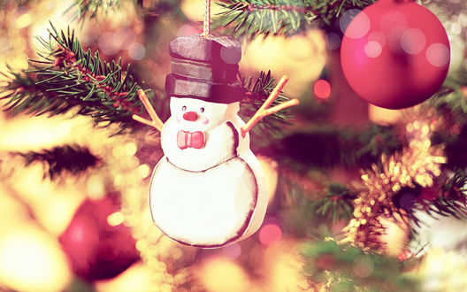 Обои Ёлочное украшение - снеговик и красные новогодние шары висят на наряженной ёлке