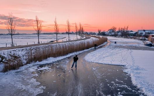 Обои Небольшая речка, проходящая вдоль дороги, превратилась в зимний каток на котором катаются на коньках люди