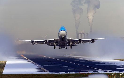 Обои Пассажирский самолет производит взлет с взлетно-посадочной полосы аэродрома в условиях плохой видимости