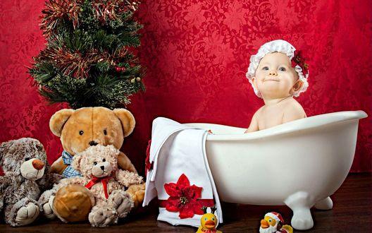 Обои Малышка в красивом белом чепчике, украшенным красным цветком, купается в ванне, возле стены лежат мягкие игрушки и стоит наряженная новогодняя елочка