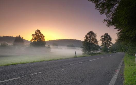 Обои Асфальтовая дорога вдоль поля покрытого утренней туманной дымкой