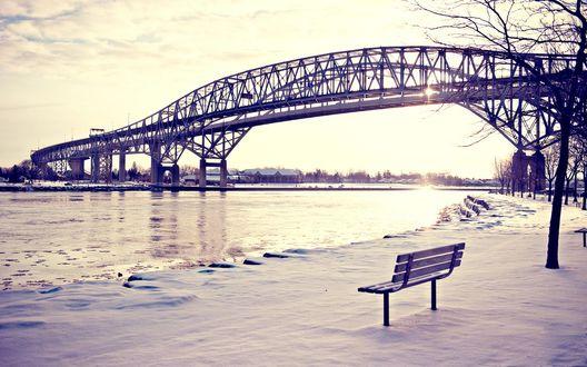 Обои Одинокая скамейка у воды, возле моста
