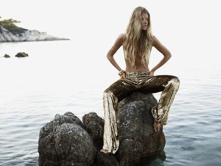 Обои Модель Даутцен Крез / Doutzen Kroes в фотосессии Джоша Олинса / Josh Olins для журнала Vogue обнаженная до пояса и в золотых штанах сидит на торчащих из воды камнях