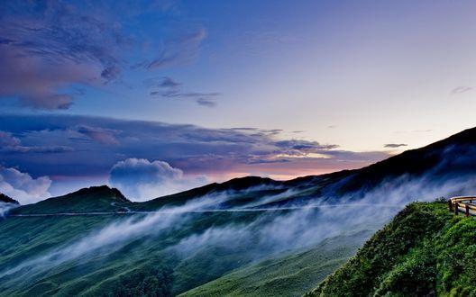 Обои Горные вершины, которые окутывают перистые облака, вдалеке виднеется дорога