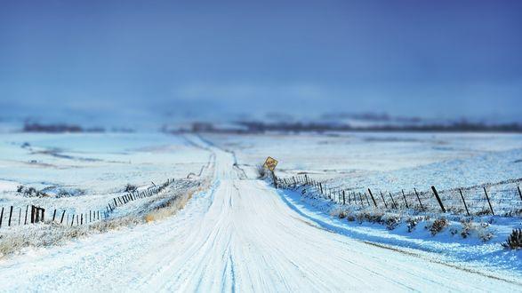 Обои Дорога, идущая вдоль снежного поля и отгороженная от него низким забором, на обочине знак 'Dead end'