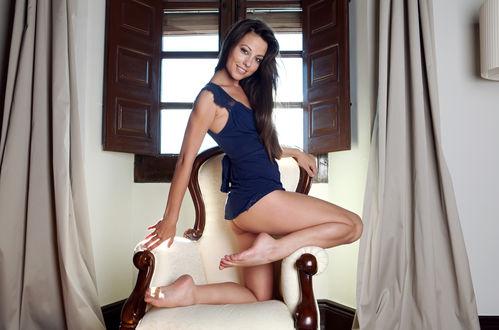 Обои Lorena Morena / Lorena Garcia / Лорена Морена / Лорена Гарсия босиком стоит коленом на бежевом подлокотнике кресла у окна со ставнями, в короткой синей майке