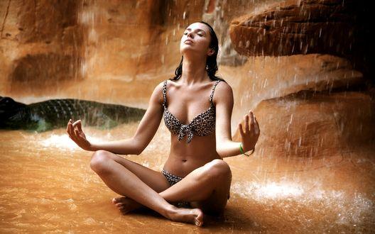 Обои Красивая девушка в купальнике занимается медитацией на фоне падающей воды горного водопада