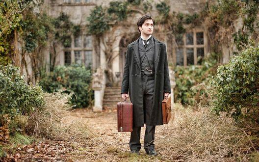 Обои Дэниел Рэдклифф / Daniel Radcliffe, стоит с двумя чемоданами в руках, позади его дом
