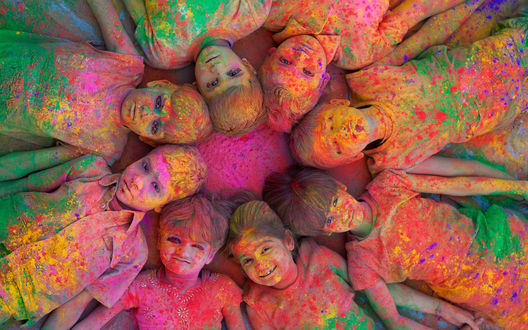 Обои Дети в разноцветной краске, лежат голова к голове создавая круг