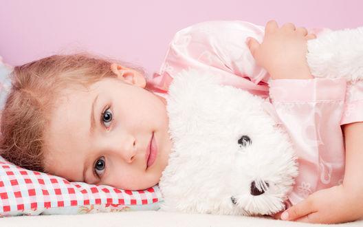 Обои Сероглазая девочка лежит на подушке с красными квадратиками, в обнимку с мягкой игрушкой-белой собачкой