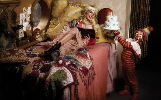 Обои Певица Бритни Спирс / Britney Spears лежит в кровати читая книгу и маленький клоун подносит к ней торт со свечами