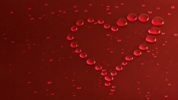 Обои Капли, сложившиеся в сердечко на красном фоне