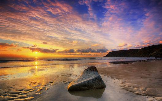 Обои Каменный валун лежит в прибрежной морской воде на фоне заката