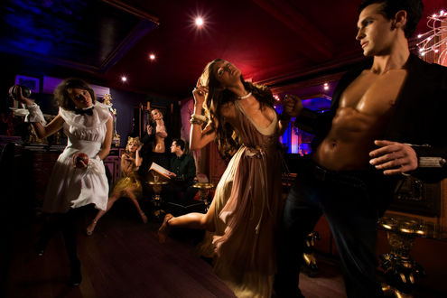 Обои Мужчина с открытым торсом и девушка в длинном платье танцуют в баре