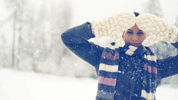 Обои Девушка в мохнатых белых варежках закрывает лицо от падающего снега