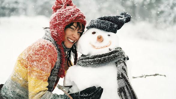 Обои Веселая девушка обнимает снеговика