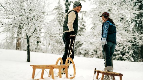 Обои Парень и девушка тянут деревянные санки на горку возле леса