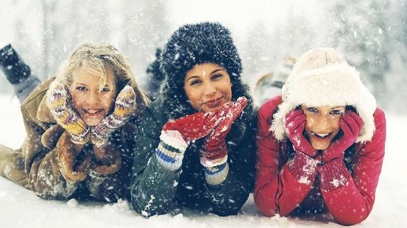 Обои Три девушки лежат на снегу