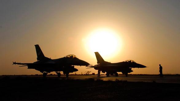 Обои Силуэты двух истребителей и мужчины-авиатехника перед взлетом на фоне заката солнца
