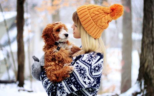 Обои Белокурая девушка в оранжевой шапочке держит на руках коричневого щенка