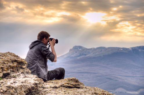 Обои Мужчина сидит на камнях и фотографирует горы