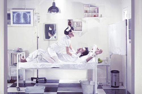 Обои Медсестра сидит сверху на прокованном к кровати пациенту и собирается ему делать укол