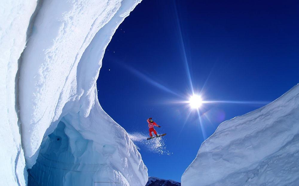 Обои для рабочего стола Сноубордист совершает красивый прыжок с крутого, снежного спуска горы